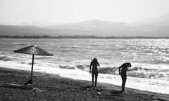 ~ Kalamia Beach (Argyro...) Tags: sea summer people blackandwhite beach water monochrome umbrella corinth greece
