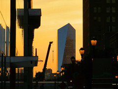 Philadelphia Street, sunset (duaneschermerhorn) Tags: orange building philadelphia glass silhouette architecture modern contrast skyscraper dark lights golden evening glow unitedstates crane pennsylvania contemporary lamps modernarchitecture lampposts contemporaryarchitecture glassfacade