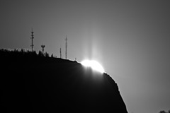 Black Knight Mountain at Sunrise 1 (LongInt57) Tags: morning sky bw white canada black mountains radio grey dawn mono shine bc okanagan towers gray silhouettes hills glowing rays kelowna sunrises shining antennae transmitters