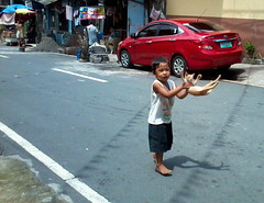 cat playing with kid (mikeeliza) Tags: street boy playing cat photography air philippines manila filipino thrown mikeeliza