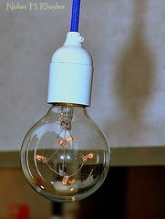 Lighting Up An Idea (nrhodesphotos(the_eye_of_the_moment)) Tags: shadow reflection glass metal bulb wire bokeh electricity filament socket glassware electricelectric nrhodesphotosyahoocom wwwflickrcomphotostheeyeofthemoment dsc27721