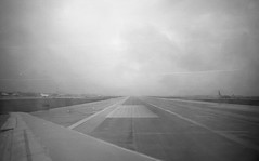 [rainy runway] (world wide flan) Tags: atlanta bw white black film monochrome rain analog plane ga georgia lens airplane puddle 50mm fly flying airport fuji cloudy atl wing jet olympus om10 off iso rainy 400 take 28 puddles runway