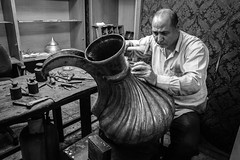 Motifs are being hammered on a giant copper pitcher (Mustafa Selcuk) Tags: street blackandwhite bw monochrome turkey handmade streetphotography monochromatic istanbul fujifilm ottoman sb bnw sokak 2016 eminonu siyahbeyaz mays xpro2 buyukvalidehan hanlar 16mmf14