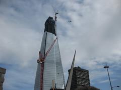 TOUCHING THE CLOUDS (RubyGoes) Tags: uk blue windows light england sky orange white building london clouds plane buildings lights construction crane cranes architect gb shard renzopiano shardofglass
