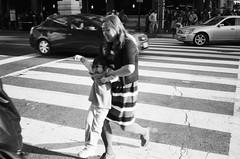 Safe Crossing (Eric Spiegel) Tags: city urban blackandwhite woman usa film analog washingtondc dc washington kid districtofcolumbia child unitedstates mother streetphotography parent intersection 135 crosswalk carry parenting carrying contaxt2 aristapremium400
