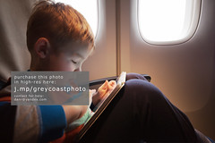 Child using tablet computer during flight (creativemarket.photo) Tags: trip travel boy people game window horizontal modern plane computer airplane fun person pc kid cabin portable alone child play little seat board flight pad lap entertainment electronics use wireless leisure activity knee tablet playful tab touchscreen touchpad illuminator