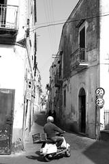 Procida - Amalfi Coast - Italy - 2016 (BirdyFlyAway) Tags: street houses people blackandwhite italy white signs man black lines car automobile exposure italia noir vespa noiretblanc streetlights perspective scout move human second ruelle moment rue blanc personnes neighbourhood italie levels homme mouvement panneaux mov casque scouter mouvants scoutter