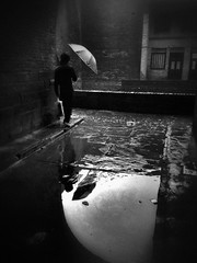 waiting for a break in the rain~ Pingyao (~mimo~) Tags: china city blackandwhite man reflection water rain weather mobile wall umbrella dark puddle photography ancient shanxi pingyao iphone jinzhong mimokhair
