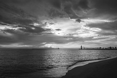 Across the sea (olsonj) Tags: light lighthouse beach water wisconsin clouds sunrise lakemichigan