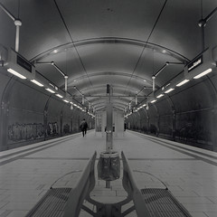 Urban Solitude - Walking down the Platform (ucn) Tags: platform bahnhof trainstation sbahn frankfurtammain bahnsteig planar80mmf28 rolleiflexsl66 agfacopexrapid caffenollccn