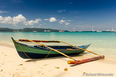 A small outrigger style Banca boat rests on a tropical beach (WhitcombeRD) Tags: ocean travel blue sea summer vacation sky holiday mountains hot tourism beach nature water beauty weather season landscape asian island bay coast boat wooden fishing sand asia quiet desert crystal native traditional small philippines relaxing peaceful sunny calm canoe resort clear explore shore tropical destination coastline camiguin boracay southeast simple idyllic climate scenics banca mindanao palawan outrigger