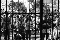 Crowd at the cathedral gate (David Gabriel Moreno) Tags: people blackandwhite church monochrome bars df gate worship cathedral prayer religion pray crowd christianity catholicism saigon hochiminhcity hcmc