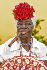 Mercedes (Simone Della Fornace) Tags: old travel flowers red portrait woman white beautiful face yellow fan dress sony traditional havana cuba culture photojournalism documentary lifestyle cigar jewelry cuban ritratto touristic a7rii