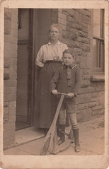 Boy with a scooter (c.1910) (pellethepoet) Tags: boy child postcard mother son scooter doorway photograph rppc realphotopostcard