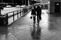 Under The Umbrella (dFederico) Tags: street winter shadow urban blackandwhite bw woman man reflection love blancoynegro blanco girl monochrome rain umbrella 35mm walking couple noir fuji sweden stockholm candid negro documentary blonde fujifilm streetphoto monochrom blanc nero streetphotographer apsc streettogs x100s dfederico