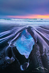 Ice Torpedo (Sairam Sundaresan) Tags: ocean sunset sea color ice beach nature colors landscape iceland waves sony wideangle iceberg oceans streaks jokulsarlon sairam sundaresan sairamsundaresan sonya7rii