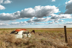 Nothing Changes But the Sky (garshna) Tags: abandoned abandonement bluesky blue clouds classiccars decayed deserted destroyed derelict door decaying dusty easternwashington environment forgotten field fence grasses isolated junkcars landscape neglected nikon old oldcars ruins rusty rust red sky sagebrush weathered washingtonstate