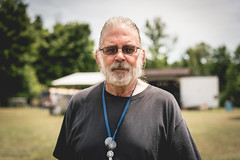 The People of Peace Fest (pooshda) Tags: old portrait people sun man green love senior beauty sunglasses hippies contrast beard person golden cool glow michigan sony hippy clarity happiness naturallight 55mm highkey aged dynamicrange alpha 18 a7 whitehair greyhair sharpness peacefest tacksharp a7r zess a7rii