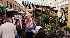 Scarlet Blooms And Citrus (dhcomet) Tags: flower london hat market crowd shoreditch citrus bouquet oranges wateringcan columbiaroad
