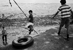 Fun with a Tyre (copperknob2011) Tags: blackandwhite film children fun filmcamera tyres olympustrip warsash blackandwhitefilm monicaweller