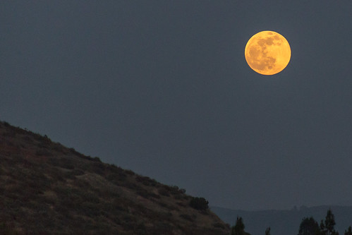 Orange full moon above the mountain