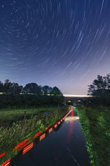 "20131115_F0001: In the middle of the ""river"" star-trails (wfxue) Tags: road city longexposure bridge trees sky lake reflection wet water grass night train river lights star cycling pond waves path lawn trails canterbury viaduct footpath starry startrails flooded polaris stour hambrookmarshes greatstour greatstourway"