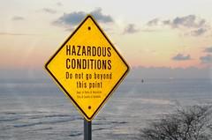 Hazardous Conditions (Jason Fairbairn Photography) Tags: ocean sunset usa water sign waves waikiki oahu dusk streetsign honolulu hazard waikikisunset