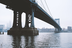Manhattan Bridge (Guillermo Murcia) Tags: nyc newyorkcity morning bridge blue usa newyork color film water fog brooklyn analog america river outdoors saturated nikon kodak manhattan dumbo engineering f100 icon nikonf100 transportation commute eastriver gotham urbanism ektar 3570mmf28 capitaloftheworld newyorkcityboroughs guillermomurcia