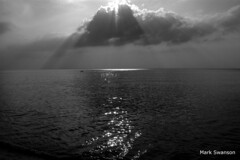 Sun and Clouds (mswan777) Tags: sunset bw white lake seascape black bird beach nature clouds landscape sand nikon exposure waves d70 michigan dunes rays