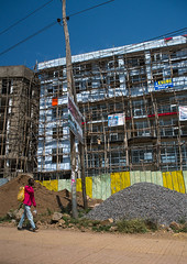 Construction of skyscrapers in the city center, Addis abeba region, Addis ababa, Ethiopia (Eric Lafforgue) Tags: life africa road street city house man color building home sign vertical skyscraper outdoors living town site scaffolding realestate apartment flat adult african engineering daily billboard company aid future globalization housing ethiopia economic constructionsite addisababa addis development investment collaboration rises oneperson builder cooperation hornofafrica ethiopian eastafrica abyssinia urbanscene residentialbuilding buildingexterior addisabeba 1people addisabebaregion ethio163240