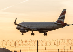 British Airways A320 sneaks in over the wire (Jez B) Tags: sunset london plane fence airplane airport wire heathrow wheels jet aeroplane landing finals short airbus british passenger ba airways approach left 27 barbed runway airliner lhr a320 undercarriage 27l a320232wl