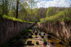 A man made canal (modestmoze) Tags: blue trees red sky plants brown white green nature wet water grass lines clouds river outside outdoors grey canal spring warm day shadows view squares branches may sunny fresh graffitti manmade walls cubes narrows lithuania vilnius silt 2016 500px