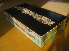 TAVOLO basso ricavato da materiale di recupero (un cassetto+un asse di legno) con funzione di baule. Il piano del tavolo è composto da un collage di foto d'epoca su sfondo nero'