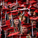 A student smiles from out in a sea of red caps and gowns during the spring 2014 commencement exercises in PNC Arena.