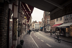 Moeder Babelutte (Gilderic Photography) Tags: street trip travel autumn houses people woman cinema brick bicycle architecture automne canon eos moving movement europe raw belgium belgique belgie shops bruges cinematic rue velo 500d gilderic