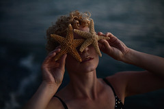 With stars in her eyes.  308/365 (aleah michele) Tags: starfish star stars fallingstar starfishonface starsinhereyes sad melancholy sea ocean water waves dark gold golden sparkle stardust shootingstar infinite dance slow simple nothing quiet inhale exhale goldenlight sunset bluehour darksky lovely beautiful vulnerable vibrant victory seashell magical magic mermaid story shore soft soul siren onceuponatime fairytale face fantasy anonymous aleahmichele aleahmichelephotography adventure abandoned 365 365project emotion emotional emerge empty eye evening emotive galaxy goldenhair curlyhair lips conceptual conceptualportrait concept calm chill christian fineart