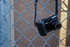 A Nikon P5100 Hanging on a Chain Link Fence (ricko) Tags: camera fence hanging nikonp5100