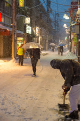 Tokyo Shopping Street In Winter (aeschylus18917) Tags: road street winter snow cold japan night 50mm tokyo pedestrians   shovel snowfall umbrellas  snowshovel shoppingstreet  danielruyle aeschylus18917 danruyle druyle