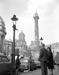 Grey's Monument, Newcastle upon Tyne (Tyne & Wear Archives & Museums) Tags: road boy shadow woman cloud dog abstract man heritage cars industry window monument glass car wheel metal standing buildings hair walking fur handle glasses daylight clothing interesting shoes pattern unitedkingdom pavement mark coat curtain social suit lamppost dome frame signage archives vehicle conversation motor shorts products gutter 1960s unusual parkingmeter cigarettes glimpse lead tyneside crease greystreet consumerism impressive streetview numberplate businesses newcastleupontyne fascinating digitalimage premises industrialheritage greysmonument blackandwhitephotograph northeastofengland artanddesign dailylives november1963 ymcabuilding turnersltd scenicviewsofnewcastle