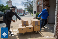 Imam Hassan and IRUSA staff help to wheel in Ramadan food boxes at Masjid ul Haqq in Baltimore, Maryland