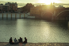 Sunset over Triana Bridge (josemanuelerre) Tags: city bridge houses friends light sunset people sun sunlight amigos luz sol water reunion backlight ro river contraluz landscape puente atardecer sevilla andaluca guadalquivir agua chat warm quiet view friendship gente talk ciudad paisaje neighborhood together shore vista postal casas barrio amistad juntos andalusian triana orilla rayos andaluz tranquilo hablar isabelii clido charlar