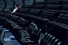 Sitting Still (TheCozyEscape) Tags: portrait people woman black sports lines person fan chair alone chairs stadium empty seat perspective environmental tunnel depthoffield arena story seats lone environment lonely bleachers bleacher leading environmentalportrait leadinglines