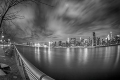 Fishy City (Elyssa Drivas) Tags: park city nyc newyorkcity longexposure nightphotography sky blackandwhite newyork building water weather skyline architecture night clouds canon buildings lights cityscape skyscrapers outdoor manhattan lowereastside east midtown eastriver empirestatebuilding gothamist eastside highdynamicrange lowermanhattan darksky gantryplaza gantryplazastatepark