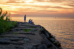 Sunset on the Breakwall (HJharland5) Tags: sunset ohio sky people lake tree water clouds boats evening fishing rocks lakeerie outdoor cleveland serene breakwall