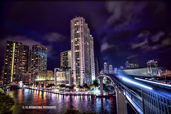 Revitalize (TIA International Photography) Tags: city railroad bridge light sky urban cloud storm motion blur reflection building tree tower art home public water rain architecture modern night skyscraper train silver tia river private landscape real hotel evening office spring long exposure downtown cityscape estate apartment purple metro florida cloudy miami district violet property rail railway stormy palm neighborhood business condo transportation april late metropolitan condominium riverwalk tosin springtime brickell miamidade metromover arasi tiascapes tiainternationalphotography
