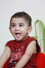 Cute and Naughty expressions  [MR] (Engineer J) Tags: old pakistan boy red portrait baby smile kids one funny year indoor junaid m playful lahore rashid islamabad uet bahawalpur engr sarim img0734 gettyimagesmiddleeast