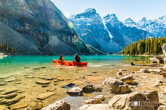 Paddling Moraine Lake (Steve Rosset) Tags: travel red people sun lake canada mountains fall water landscape fun rockies couple outdoor weekend turquoise scenic paddle floating ab tourist canoe adventure clear alpine retreat alberta lensflare flare moraine kanada morainelake