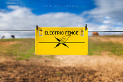 Electric fence sign (Robert Lang Photography) Tags: blue brown green sign yellow electric danger rural warning fence ouch wire power cattle sheep beware farm farming stock caution signage shock fencing agriculture electrical livestock spark volts voltage agribusiness notouch