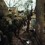 17 Feb 1968, Hue - U.S. Marines, seen from behind, sneaking between destroyed houses in a village. thumbnail