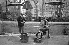 Street Music (DRodino) Tags: street nyc bw music men film public musicians analog drums pentax k1000 performance pentaxk1000 bagpipes umbrellas unionsquare